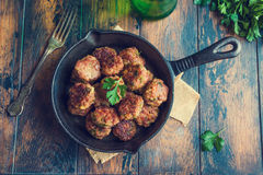 Homemade roasted beef meatballs in cast-iron skillet on wooden table in kitchen, fresh parsley, vintage fork, top view Stock Images