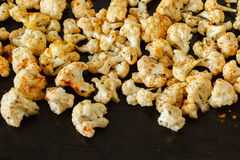 Roasted cauliflower on a table. Homemade roasted cauliflower with turmeric and herbs Royalty Free Stock Image