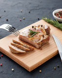 Homemade roasted pork meat on cutting board with cutlery, herbs and spices. Stock Photo