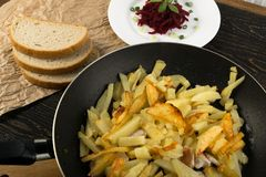 Homemade Roasted Potato in a Frying Pan on Rustic Background. Close Up and Top View. Golden Hot Baked Slices of Spud with Sunflower Oil, and Beet Root Salad and stock photo
