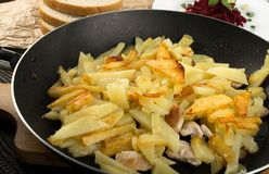 Homemade Roasted Potato in a Frying Pan on Rustic Background. Close Up and Top View. Golden Hot Baked Slices of Spud with Sunflower Oil and Bread stock photo
