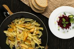 Homemade Roasted Potato in a Frying Pan on Rustic Background. Close Up and Top View. Golden Hot Baked Slices of Spud with Sunflower Oil, and Beet Root Salad and stock photography