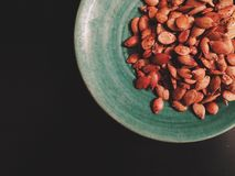 Homemade roasted pumpkin seeds on green plate. Homemade roasted pumpkin seeds are served on a green stoneware plate, shot top down on a black background Stock Photos