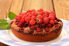 Homemade round chocolate cake with fresh raspberries and green l. Eaves in white plate on wooden table closeup Stock Photos