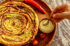 Homemade round vegetable pie served with cherry tomatoes, chili pepper and sesame seeds in pot, female hand holding a wooden spoon Stock Photography