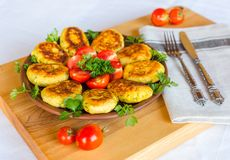 Homemade ruddy cheese and potato cutlets, decorated with fresh tomatoes and parsley, in ceramic plate on wooden board stock photography