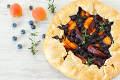 Homemade rustic fruit galette. Summer fruits homemade galette made with apricots, peaches and blueberries Royalty Free Stock Photography