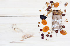 Homemade rustic granola bars. With dried fruits and handmade packaged and cup of coffee on wooden background Stock Photo