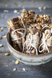 Homemade rustic granola bars with dried fruits and handmade packaged on vintage bowl Stock Photo
