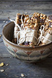 Homemade rustic granola bars with dried fruits and handmade pakaged on old bowl Stock Image