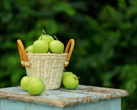 Homemade rustic green apples in a basket on an old stool. Stock Photos
