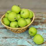 Homemade rustic green apples in a basket on an old stool. Selective focus Stock Photography