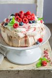 Homemade and rustic Pavlova cake with raspberries and meringue. Closeup of homemade and rustic Pavlova cake with raspberries and meringue Stock Photography