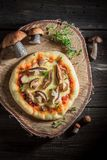 Homemade rustic pizza with noble mushrooms and thyme Royalty Free Stock Photo