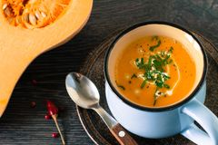Homemade rustic pumpkin soup. Pumpkin soup with cream and parsley on dark wooden background Stock Photo
