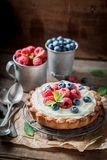 Homemade and rustic tart with mascarpone cheese and fruit. On old wooden table royalty free stock image