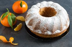 Homemade rustic winter orange cake. On dark table Stock Images