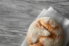 Homemade rye artisan sourdough bread. Over white wooden background. Top view of bread represented on cooking paper. Blank copy space for noting your ideas and Royalty Free Stock Photo