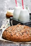 Homemade  rye bread  on baking paper and bottles of milk on woode. Homemade  rye bread on baking paper and bottles of milk on wooden table Royalty Free Stock Photography