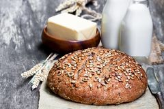 Homemade  rye  bread on baking paper and bottles of milk on woode. Homemade  rye bread on baking paper and bottles of milk on wooden table Royalty Free Stock Images