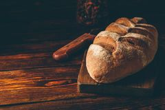 Rye bread with knife. Homemade rye bread on cutting board with knife over dark wooden background stock photography