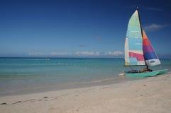 Homemade Sailboat on the Beach. Multi-colored sailboat on a sandy island beach Stock Photography