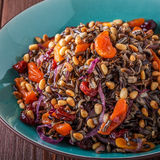 Homemade salad with wild rice, dried fruit and pine nuts. Stock Images