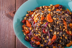 Homemade salad with wild rice, dried fruit and pine nuts. Royalty Free Stock Photography