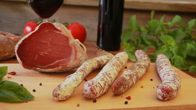 Homemade salami jerky sausages with a glass of red wine stock video
