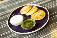 Homemade Salty Cheese Pancakes. With sauce Pesto. Cheesecake pancakes with sour cream. Pancakes photographed close Royalty Free Stock Photo