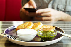 Homemade Salty Cheese Pancakes. With sauce Pesto. Guy with the phone on the background. Pancakes photographed close Royalty Free Stock Photos