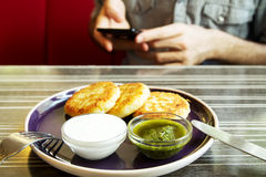 Homemade Salty Cheese Pancakes. With sauce Pesto. Guy with the phone on the background. Pancakes photographed close Stock Photos