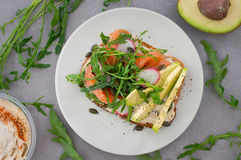 Homemade sandwich with avocado, salmon, arugula and humus. Rustic style. Gray stone background. Close-up. Top view Royalty Free Stock Photos