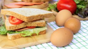 Homemade sandwich breakfast preparing. Close up whole wheat sandwich bread with slice tomatoes and lettuce stacked on wooden cutti royalty free stock images