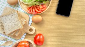 Homemade sandwich breakfast preparing. Whole wheat bread is stacked on a wooden cutting board placed on a white fabric, green chec stock photos