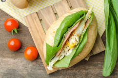 Homemade sandwich with ham, eggs, cheese and vegetables on white. Wooden table background Royalty Free Stock Images