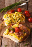 Homemade sandwich with scrambled eggs, bacon and tomatoes close- Royalty Free Stock Image