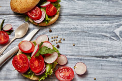 Homemade sandwiches with tomato, onion, radishes, parsley. Healthy food concept. Tasty homemade sandwiches with tomato, onion, radishes, parsley, on a wooden Royalty Free Stock Images