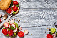 Homemade sandwiches with tomato, onion, radishes, parsley. Healthy food concept. Tasty homemade sandwiches with tomato, onion, radishes, parsley, on a wooden Stock Image