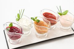 Homemade sauce assorted glass gravy boat platter. Homemade sauces composition. Assorted glass gravy boats on white platter royalty free stock photography