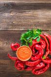 Homemade sauce and red hot chili peppers and celery. On rustic wooden background. Top view Royalty Free Stock Images