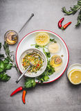 Homemade sauce or salad dressing in bowl with ingredients:  fresh herbs, oil, lemon and honey on gray concrete background, top vie Royalty Free Stock Images