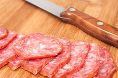 Homemade sausage cut into slices and served on the board and kni Stock Photography