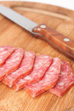 Homemade sausage cut into slices and served on the board and kni Royalty Free Stock Image