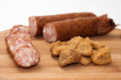 Homemade sausage and pork scratchings served on a kitchen board Stock Photos