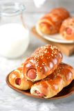 Homemade sausages in dough with sesame and a jug of milk on a gray background. Stock Images