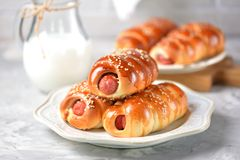 Homemade sausages in dough with sesame and a jug of milk on a gray background. Stock Photo