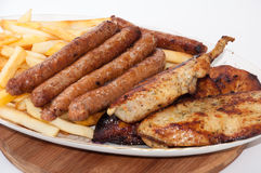 Homemade sausages and grilled meat served with french fries Royalty Free Stock Images