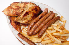 Homemade sausages and grilled meat served with french fries Royalty Free Stock Photos
