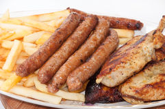 Homemade sausages and grilled meat served with french fries Stock Photo